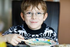 Beautiful little school boy eating vegetable soup indoor. Blond child in domestic kitchen or in school canteen. Cute kid and healthy food, organic vegan soup Stock Photos
