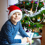 Little school kid boy reading a book on Christmas Stock Image