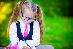 Beautiful little schoolgirl writing with pencil Royalty Free Stock Photography