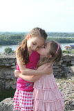 Beautiful little sisters are kissing Royalty Free Stock Images