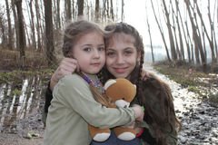 Beautiful little sisters pose with teddy bear. In forest and smiling stock photos