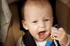 Beautiful little smiling baby in a baby carriage on the streets Stock Image