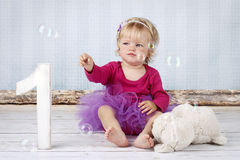 Beautiful little toddler catching bubbles. And celebrating her first birthday, studio portrait Royalty Free Stock Images