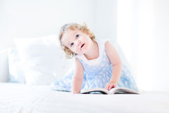 Beautiful little toddler girl with curly hair reading book Royalty Free Stock Photos