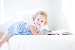 Beautiful little toddler girl with curly hair reading book Royalty Free Stock Image