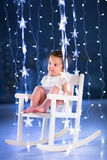 Beautiful little toddler girl in a dark room with Christmas lights Stock Photography