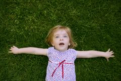 Beautiful little toddler girl happy lying on grass Stock Photo