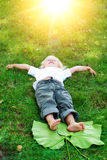 Beautiful little toddler girl happy lying on grass Royalty Free Stock Photography