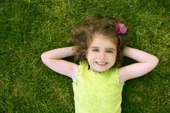 Beautiful little toddler girl happy lying on grass stock images