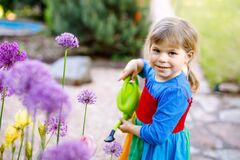 Free Beautiful Little Toddler Girl In Yellow Rubber Boots And Colorful Dress Watering Spring Flowers With Kids Water Can Royalty Free Stock Image - 183273826