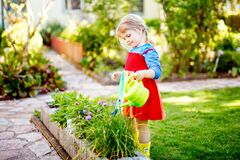 Free Beautiful Little Toddler Girl In Yellow Rubber Boots And Colorful Dress Watering Spring Flowers With Kids Water Can Stock Photos - 211724403
