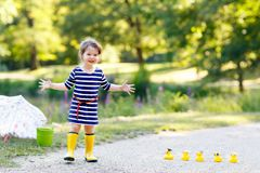Beautiful little toddler girl playing in park. Adorable child wearing fashion casual clothes and yellow rubber boots. Happy childhood. Kid playing with toy royalty free stock photo