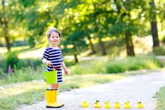 Beautiful little toddler girl playing in park. Adorable child wearing fashion casual clothes and yellow rubber boots. Happy childhood. Kid playing with toy royalty free stock images