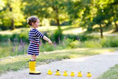 Beautiful little toddler girl playing in park. Adorable child wearing fashion casual clothes and yellow rubber boots. Happy childhood. Kid playing with toy stock image