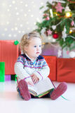 Beautiful little toddler girl reading a book sitting under a dec Stock Photos