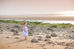 Beautiful little toddler girl watching the sunset  Royalty Free Stock Image