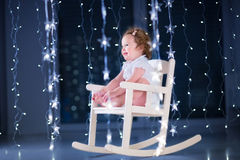 Beautiful little toddler girl  in a white rocking chair in a dark room with Christmas lights Stock Images