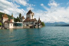 Beautiful little tower of Oberhofen castle in the Thun lake with. Mountains on background in Switzerland, near Bern royalty free stock photo