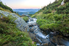 Beautiful little waterfall in mountains with white foamy silky w stock image