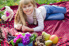 Beautiful little young baby lies on a red plaid. Lovely child smiling with bright flowers Stock Image