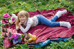 Beautiful little young baby lies on a red plaid. Lovely child smiling with bright flowers Stock Photography