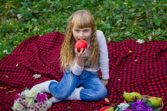 Beautiful little young baby in a pink hat with an apple in his hand. Beautiful child sitting on a red plaid. Stock Images