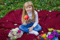 Beautiful little young baby in a pink hat with an apple in his hand. Beautiful child sitting on a red plaid. Royalty Free Stock Photos