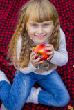 Beautiful little young baby in a pink hat with an apple in his hand. Beautiful child sitting on a red plaid. Royalty Free Stock Image