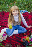 Beautiful little young baby in a pink hat with pear in hand. Beautiful child sitting on a red plaid. Stock Photo