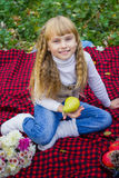 Beautiful little young baby in a pink hat with pear in hand. Beautiful child sitting on a red plaid. Royalty Free Stock Photography