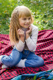 Beautiful little young baby sitting on a red plaid. Lovely child smiling with bright flowers Stock Photo