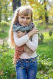 Beautiful little young baby stands in a scarf. Lovely child smiling Stock Images