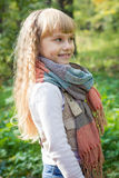 Beautiful little young baby stands in a scarf. Lovely child smiling Royalty Free Stock Photography