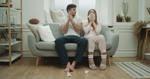 Beautiful living room modern design couple have a bad flu and runny nose they using tissue for nose , both in pajamas. stock video footage
