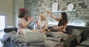 In a beautiful loft apartment three young woman s have pajamas party on the bed they cheers with champagne glasses. Smiling large stock footage