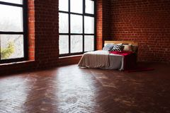 Beautiful loft bedroom with bed near brick wall and big window.  Stock Photography
