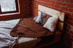 Beautiful loft bedroom with bed near brick wall and big window Royalty Free Stock Photos