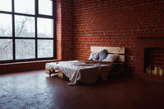 Beautiful loft bedroom with bed near brick wall and big window Stock Photos