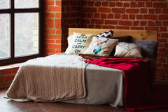 Beautiful loft bedroom with bed near brick wall and big window.  Stock Images