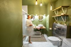 Green bathroom with woman in bathrobe stock images