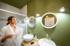 Green bathroom with woman in bathrobe stock photos