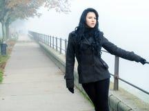 Beautiful lonely girl walking in park on misty autumn day. Beautiful lonely girl walking in the park on misty autumn day royalty free stock photos