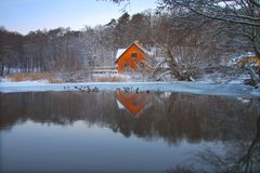 Beautiful lonely house on a lake shore in the forest mirroing the lake in wintertime with snow weather - stock image Stock Photos