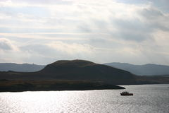 Beautiful but lonely. Image captures a small fishing boat in Loch Linnhe off the west coast of Scotland Stock Images