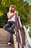 Beautiful lonely teenage girl standing on the stairs. On sunny summer day Royalty Free Stock Photography