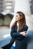 Beautiful lonely woman in city street. Beautiful lonely woman posing in city street. Crossed arms Stock Photo