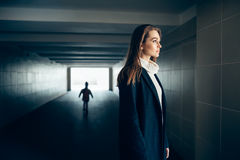Beautiful lonely woman in subway tunnel with frighten silhouette. Beautiful lonely woman in a subway tunnel with frighten silhouette on background. surrealism Stock Photo
