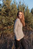 Beautiful lonely young girl with big eyes and wide bushy eyebrows in a warm sweater walking in the forest at sunset Royalty Free Stock Photo