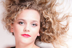 Beautiful long blond curly hair of young attractive woman royalty free stock photo