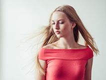Beautiful long blonde hair woman in red dress natural over white. Background. Studio shot stock images